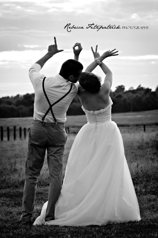 Bride and groom hold hands in the air to spell LOVE with their fingers.
