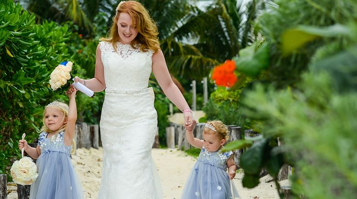 Bride and flower girls - in sweet blue dresses - hold hands as they walk down the aisle at Moon Palace Cancun #destinationwedding
