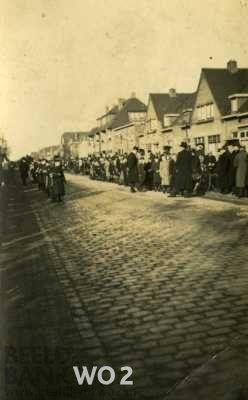 Foto van straat met bakstenen met huizen aan de rechterkant. Aan de rand van de straat staat publiek. Ervoor mannen in doodsbidder kostuum (hoge hoed, zwarte jas e.a.). Op de weg staat een kleine colonne mannen. Tekst achterop: 'Roerstraat Nijmegen'. (Noot: waarschijnlijk een foto van een deel van de processie voor de begrafenis van slachtoffers van het bombardement van 22 februari 1944).
