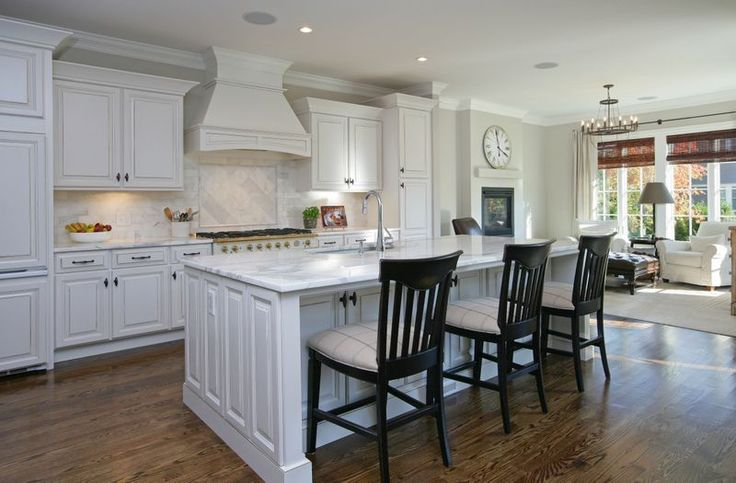 Here we have another entry in the white cabinetry style kitchen. This one features a large island with bar seating and dark toned hardwood flooring.