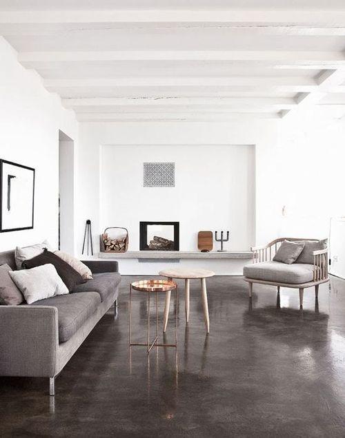 Sala de estar decorada com piso de cimento queimado e sofá cinza
