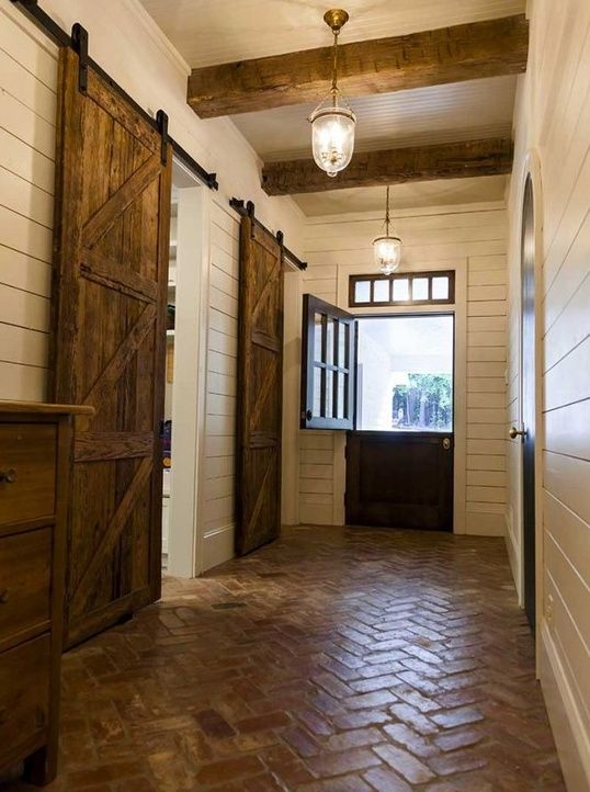 Rustic entry with brick floor, beams and barn doors.  #entryway #foyer homechanneltv.com
