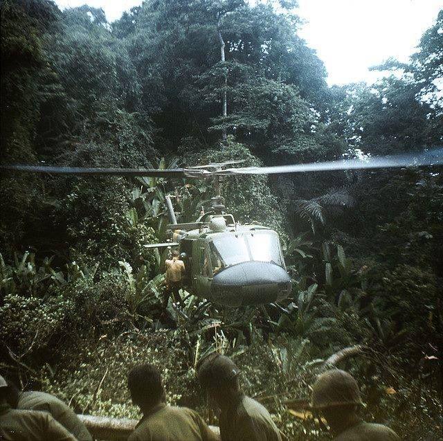 A Huey drops down into a very dense LZ in the jungle. ~ Vietnam War