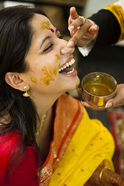 Turmeric Paste being applied to a joyful bride.