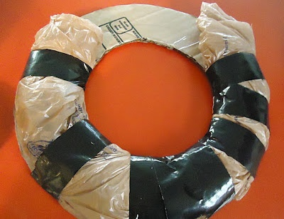 Use plastic bags, cardboard, and duct tape to create your own wreath frame. Gives it that needed shape (roundness) then just wrap and/or glue your decorations and flowers to it. -- Going to be doing this for our Fall Wreath.
