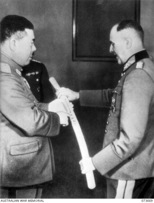 Berlin, Germany. 1941-02. General Tomoyuki Yamashita, Japanese Army, on the left, leader of a delegation of Japanese Army and Naval officers studying war strategy in Germany, translating the inscription on the scabbard of a Samurai Sword. He was making a presentation of the sword to Field Marshal Walter Von Brauchitsch, Commander-in-Chief of the German Army. ( ID number 073669)