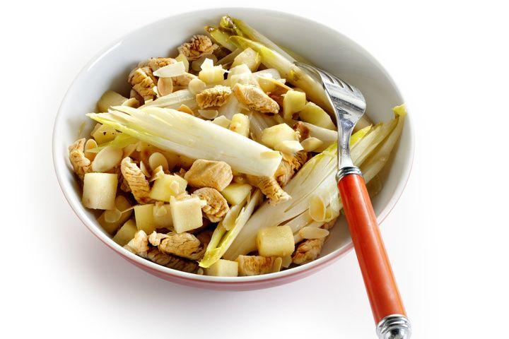 Verhit de olie en roerbak hierin de kalkoenreepjes 5 minuten. Schep de ui erdoor en bak nog 5 minuten. Voeg zout en peper toe. Sprenkel citroensap over de appel, schep de witlof en appel door de roerbakschotel en bak 3 minuten. Rooster de amandelen in een droge hete koekenpan en strooi ze voor het serveren over het gerecht. Lekker met stokbrood.