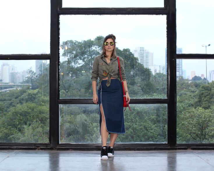SPFW N41 – Look 4 | Street Style Urbano, com jeans, tênis e patches  Camisa militar de patches, com saia jeans assimétrica, óculos espelhado, bolsa vermelha, tênis superstar adidas, coque samurai