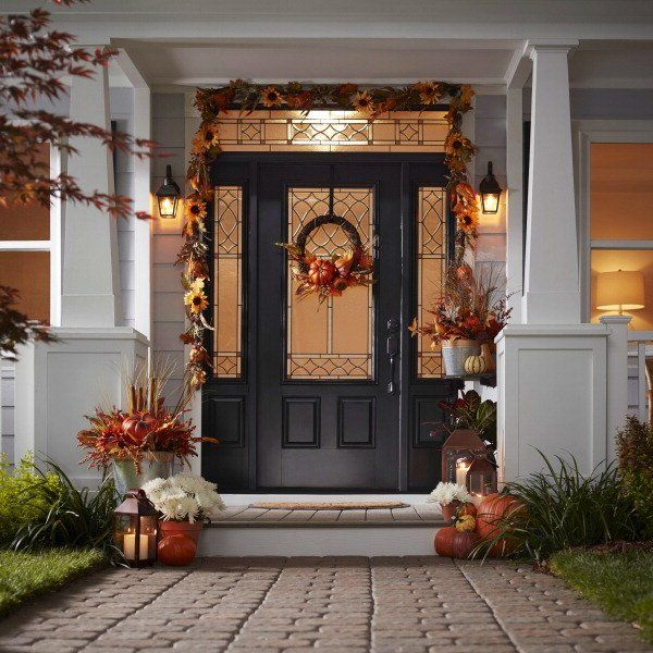 Fall curb appeal comes together with a few simple touches. An autumnal wreath coordinates with a draped garland, and stacks of pumpkins glow next to bronzed lanterns. Shop this look now.