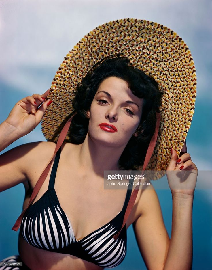 Actress Jane Russell (b. 1921) wearing a black and white bikini top while holding the wide brim of a straw hat. Color publicity handout, slide.