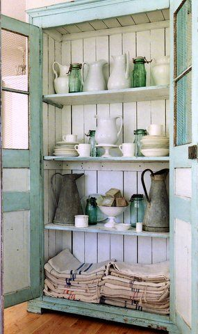 Blue and white cupboard filled with ironstone