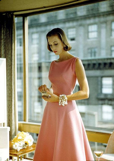 Model is wearing party dress of pink wool jersey by Pauline Trigère with wrapped ropes of dripping pearls by Mosell, photo by Nina Leen, 1954