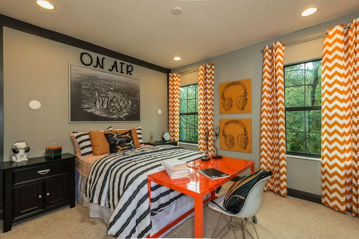 A neutral, gray teenage bedroom features a mixture of patterns: striped bedding and orange chevron curtains. An orange desk sits at the end of the bed for a contemporary workspace.