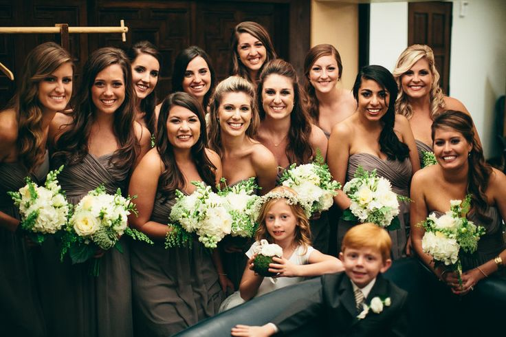 bridesmaids carry bouquets of white dahlia, white ranunculus, white rose, white hydrangea, white snapdragon , maidenhair fern, bupleurum and Queen Anne's lace.