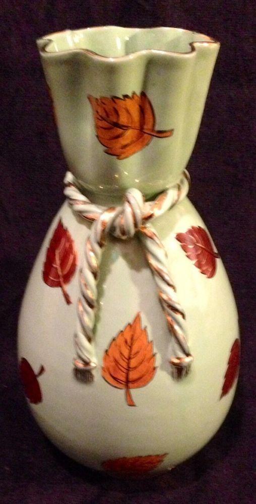 """Vaso in ceramica anni '40/'50 dalla insolita forma a fazzoletto stretto al """"collo"""". È alto 29 centimetri circa ed è di colore verde penicillina, le foglie sono marroni con finiture in oro a terzo fuoco. Anche la """"corda"""" con le nappine che simula il cappio al """"collo"""", ha le finiture in oro. Sarò di parte, ma trattasi di un vaso davvero molto bello che attende di essere concupito. Invito gli interessati a scrivermi a prescindere che la trattativa vada o meno a buon fine."""