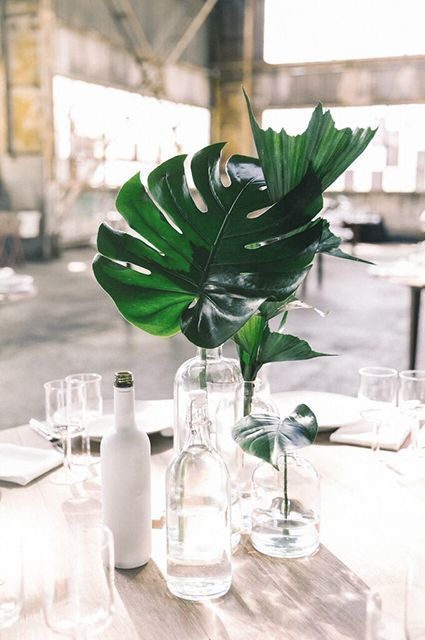 Minimalist wedding details are all about tiny things that make a noticeable difference, just like in this stylish centerpiece. The single leaves in the unassuming glass bottles are undoubtedly the center of attention, without being ostentatious.
