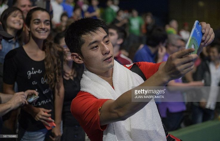 China's Zhang Jike takes a selfie photograph after beating Japan's Koki Niwa in their men's singles quarter-final table tennis match at the Riocentro venue during the Rio 2016 Olympic Games in Rio de Janeiro on August 9, 2016. / AFP / Juan Mabromata