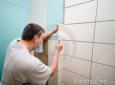 A man working at new bathroom tiles, putting them on the wall.   <a href='http://www.dreamstime.com/interiors-rcollection5192-resi208938' STYLE='font-size:13px; text-decoration: blink; color:#FF0000'><b>HOME BUILDING & RENOVATION »</b></a>