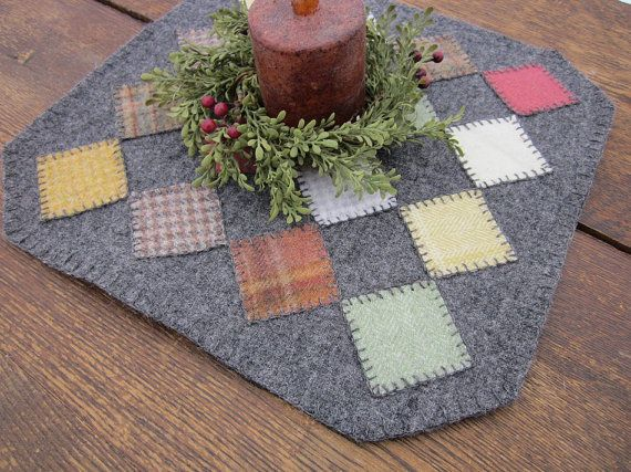 Warm colored wool fabrics are used to create this penny rug.  The base is gray wool. It is hand sewn to the gray felt backing. Two inch squares of various wool fabrics are ironed on and and hand stitched using the blanket stitch. Alpaca fingering yarn is used for all the hand stitching.  It is square, 13 by 13 inches.  Hand wash in cold water, lay flat to dry.  contact me for international postage rates.