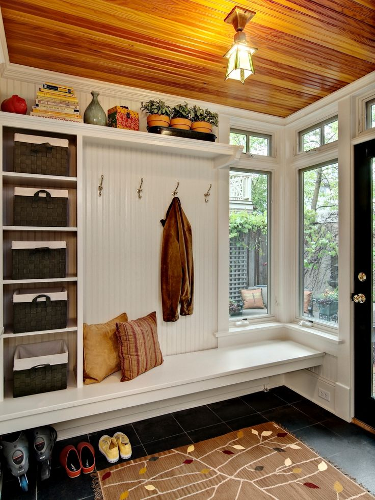 """""""Mudrooms are typically small in square footage, so make the most of the space by going vertical,"""" JoLynn Johnson says. """"Add shelves where bins and baskets can be placed for easy access. Smaller items like hats, gloves and scarves can be stored in the bins."""" This traditional mudroom offers all the storage amenities of a spacious room compacted into one unit. Storage shelves, baskets, hooks, bench seating and convenient floor storage all help keep mudroom contents tidy and within reach."""