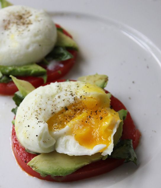 Poached eggs with tomatoes, avocado and basil.