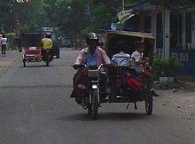 Tampak dua becak mesin sedang melintas di jalanan Medan.