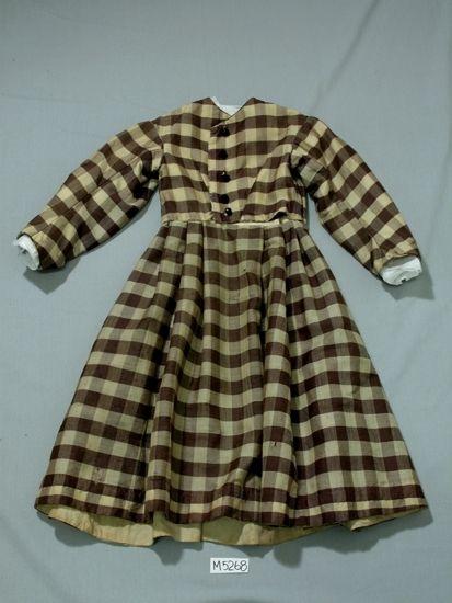 Handsydd klänning till flicka, 6-7 år.   Av brunt och vitt rutigt ylletyg.  Livet åtsittande, svarta stenkolsknappar fram (fem st.),   lång ärm.  Kjolen veckad vid midjan  Livet fodrat med linnetyg, ärmarna fodrad med grövre linnetyg.   Kjolen är fållad med en 40 mm bred remsa av linnetyg.    Inskrivet i huvudbok 1932.  Funktion: Barnklänning