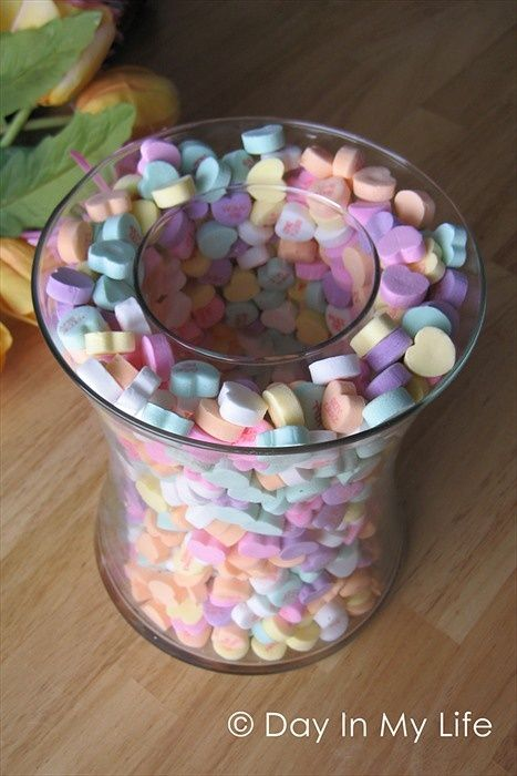 Take two different size vases and sprinkle candy hearts between them and voilà: the perfect centerpiece for your Valentine's Day party decor! (You can by cheap vases from the dollar store.)