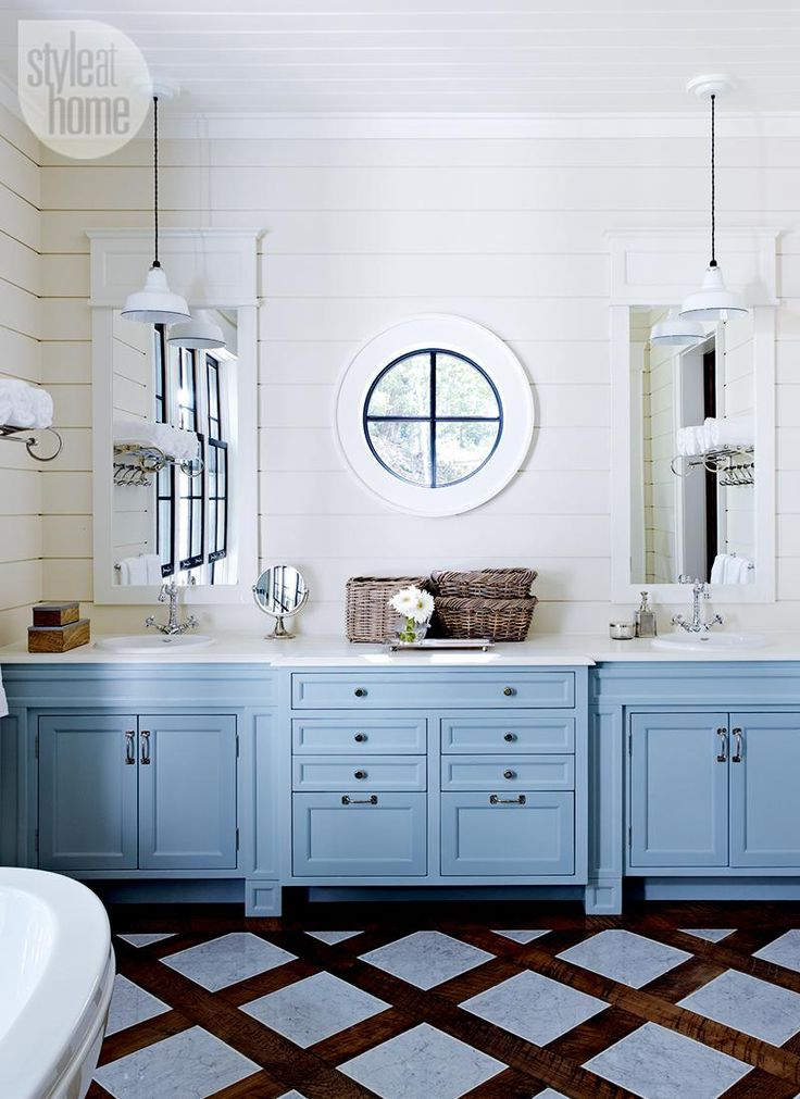 Master bathroom—In the master bathroom, Cory used a soft blue for the vanity and let the floor treatment, a wooden trellis pattern with inset marble tiles, act as the focus. The round window between the sinks is reminiscent of a ship's porthole.