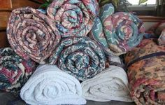 5 Unique Storage Ideas for Large Bed Linens:  • Place blankets in between your bed's mattress and box spring. The added height and cushion makes it feel like a brand new bed!  • Hang shower curtain rods in your closet behind your clothes to hang comforters.  • Fold large blankets and store them in empty suitcases.  • Roll large blankets like sleeping bags, tying them together with rope, a belt or an old phone cord.  • Finally, keep original packaging that comforters came in