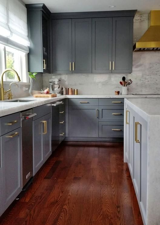 Stunning gray kitchen with gold accents boasts cherry stained oak wood floors lining gray shaker cabinets adorning brushed bras pulls and thick marble countertop fitted with a stainless steel sink and brass gooseneck faucet placed beneath a window dressed in a white roman shade.