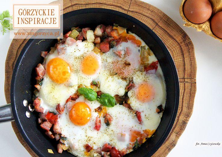 Wędzonka wieprzowa, cebula, pomidorki koktajlowe, świeża bazylia i jajka, a wszystko zapiekane w piekarniku. http://www.zmgorzyca.pl/index.php/pl/kulinarny/sniadanie/416-zapiekane-jajka