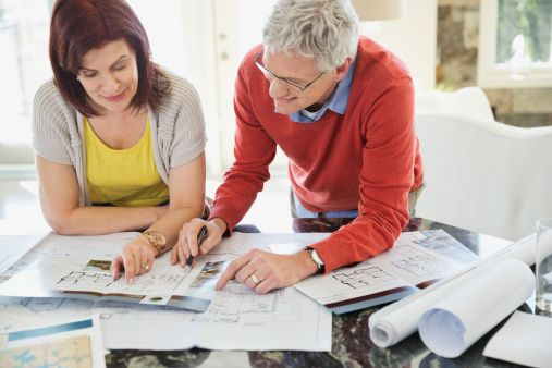 Mature couple discussing home designs in kitchen