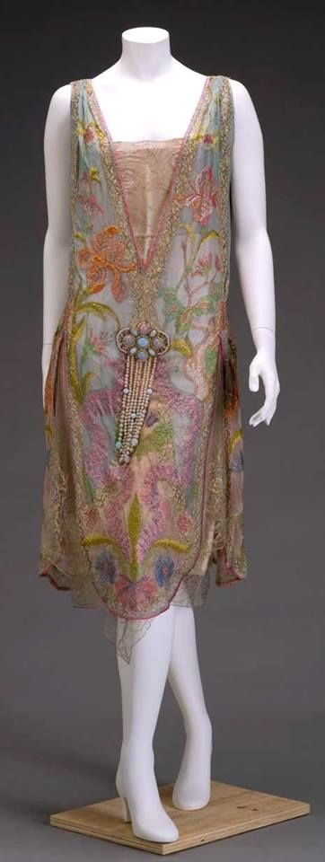 Callot Souers an elegant silk evening dress embroidered with Irises and Geum (water aven) ca 1926 Embroidered layers of soft, sheer silk decorated with embroidery and metallic lace are fixed with a large jewelled ornament of imitation pealrs and opals
