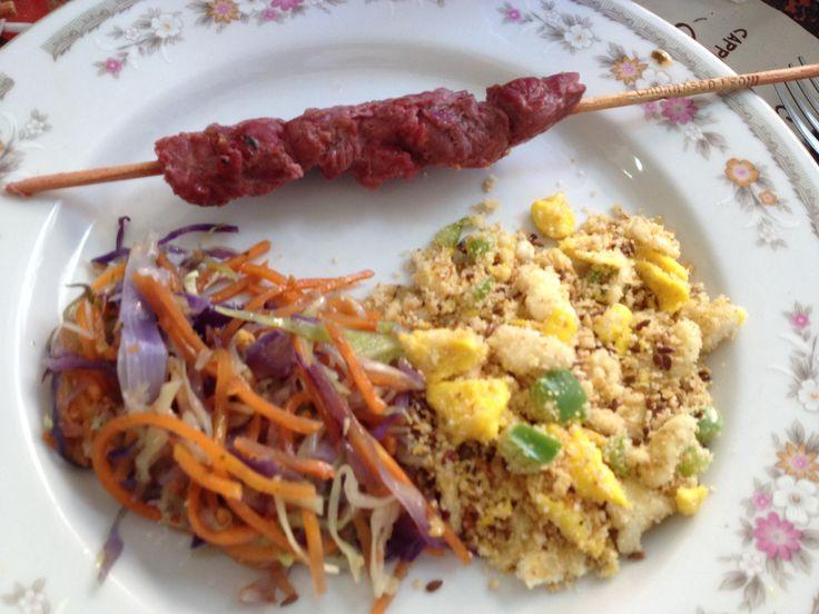 Espetinho de carne, salada mix com cenouras, repolho roxo, cebola e cheiro verde; farofa de ovos.
