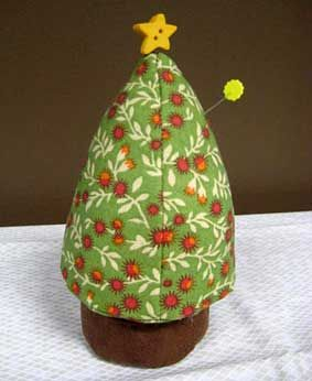 """Tree Pincushion Pattern @Connecting Threads: Free Pattern. Remind yourself of that warm holiday cheer with this cute pincushion pattern. Make two pincushions-one to keep and one to give as a gift. Sewists will appreciate the large size and shape which will hold many pins. This FREE pattern will make one Christmas tree pincushion. Techniques: piecing. 3 1/4"""" x 7"""". Item No. 991463."""