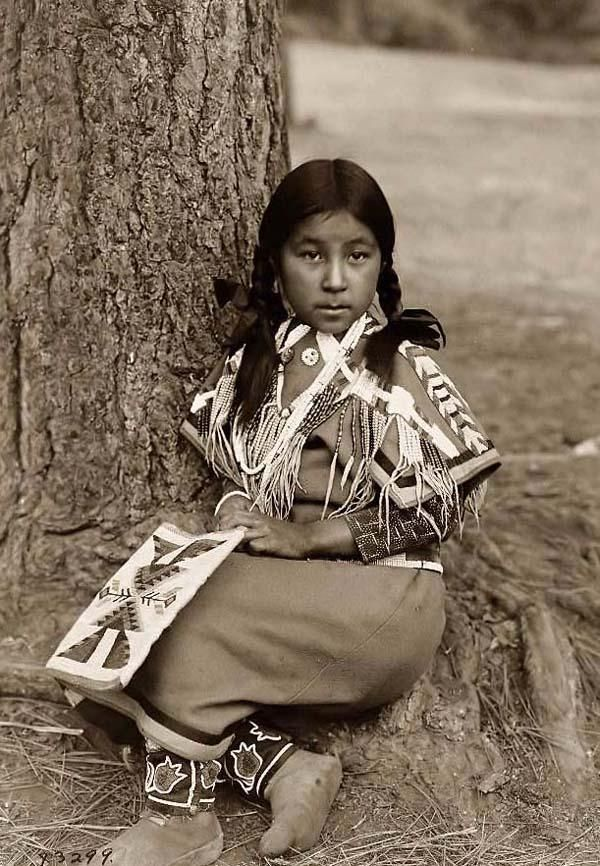 Here for your browsing pleasure is a grand photo of an Umatilla Indian Child. It was made in 1910 by Edward S. Curtis.    The photo documents Umatilla girl, full-length portrait, facing front, seated on ground by pine tree, wearing beaded blanket dress, beaded moccasins, holding beaded bag in lap.    We have compiled this collection of photos mainly to serve as a vital educational resource. Contact curator@old-picture.com.