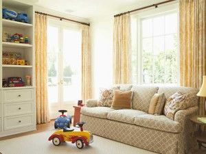 There is simple style of living room and there is cabinet on the side there is lots of toys placed on it.