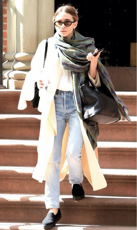 Ashley Olsen wears Trademark snake earrings with a long sweater, light-wash denim and an oversized scarf.