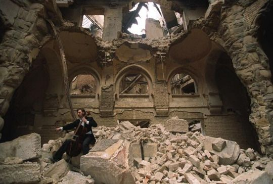 Cellist Vedran Smailovic plays Strauss inside the bombed-out National Library during the Siege of Sarajevo, 1992.