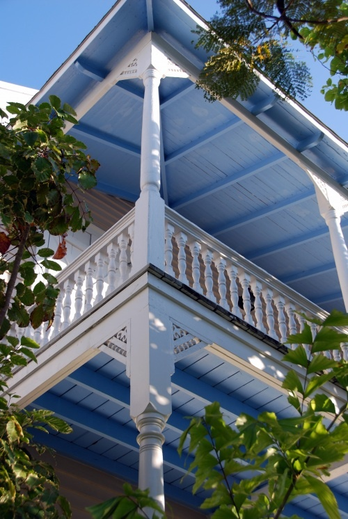 Deep 2nd floor porches on Queen Ann style Key West house is painted underneath in a robin egg blue.