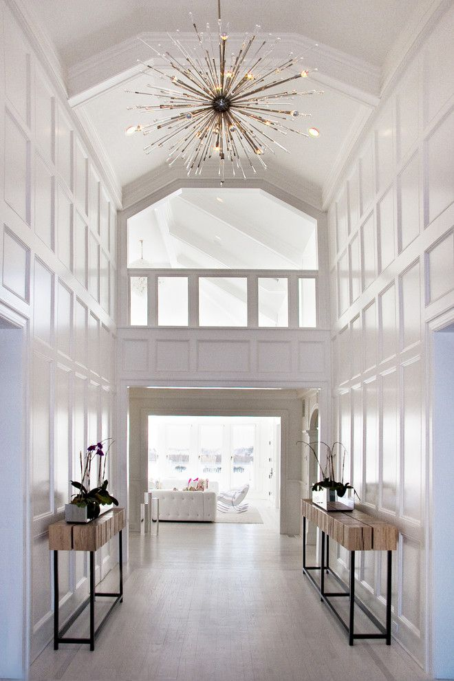 Stunning Two Story Foyer White Moulding On Walls Wood Side Tables Gladiator Spiked Chandelier