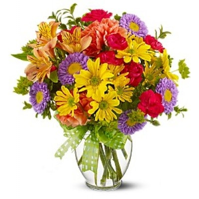 A summery mix of yellow daisy chrysanthemums, purple asters and hot pink and orange carnations - arranged in a clear ginger vase and adorned with a cheerful yellow plaid bow