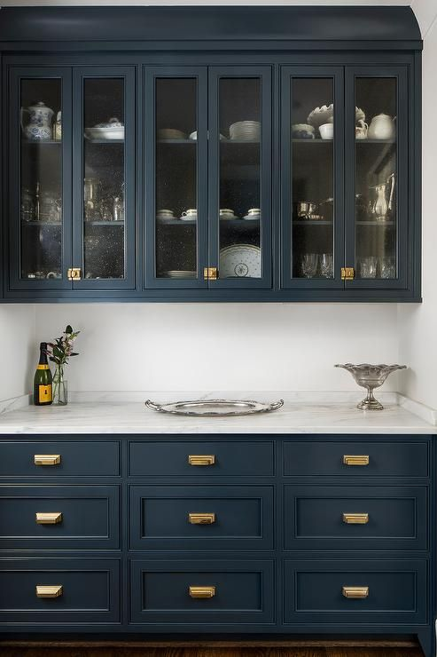 Striking royal blue butler's pantry cabinets are accented with vintage brass latch hardware and topped with a white marble countertop positioned beneath glass front royal blue upper cabinets.
