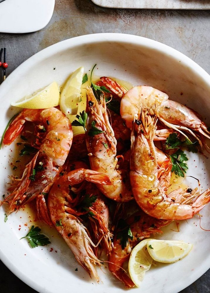 "Gambas al Ajillo | A popular tapa in Spain, gambas al ajillo means ""garlic shrimp,"" and this version lives up to its name. Three garlic cloves infuse the cooking oil, and then three sliced cloves are sautéed along with the shrimp. Red pepper flakes add a spicy kick."