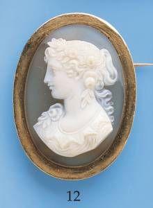 Broche  en or jaune ornée d\ un camée sardoine, représentant le buste d\ une jeune femme.  Poids brut: 16.4 g.