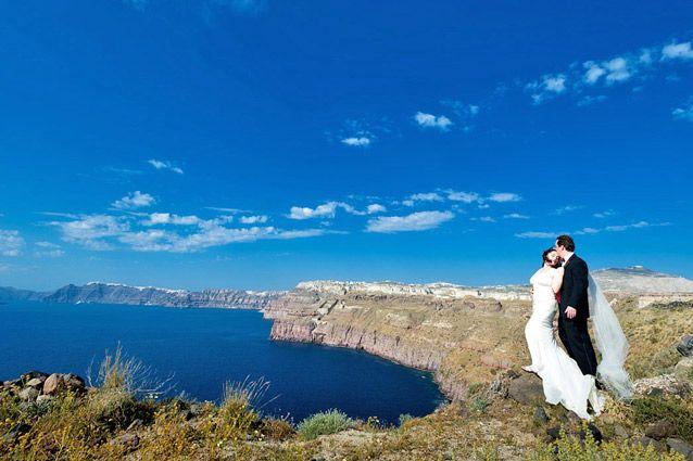 Newlywed couple enjoying the view of Santorini's caldera