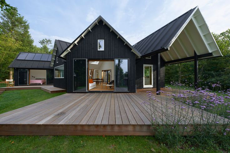 DANISH PITCHED ROOF SUMMER HOUSE BY POWERHOUSE COMPANY - The home is made up of a simple, black wooden structure with a pitched roof, almost like the dark shadows in the surrounding woods. The interior is the opposite being all white to help maximize the light.