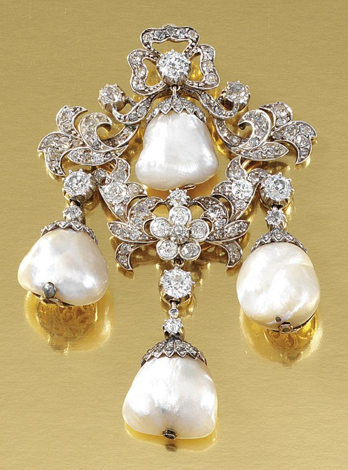 BAROQUE PEARL AND DIAMOND PENDANT/BROOCH, 1890S.  Designed as ribbon tied floral and foliate garlands, embellished with circular-cut and cushion-shaped diamonds, suspending to the centre and the three pendant drops a baroque pearl dressed by a diamond-set cap, brooch fitting deficient, collapsible pendant fitting, one diamond deficient.
