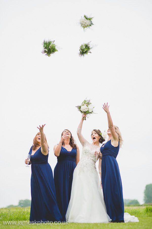Wedding Group Shot. Bride & Bridesmaids throwing flowers. Hush Venues Norfolk Outdoor Wedding Venue. Norfolk Wedding Photographer. www.jameskphoto.co.uk
